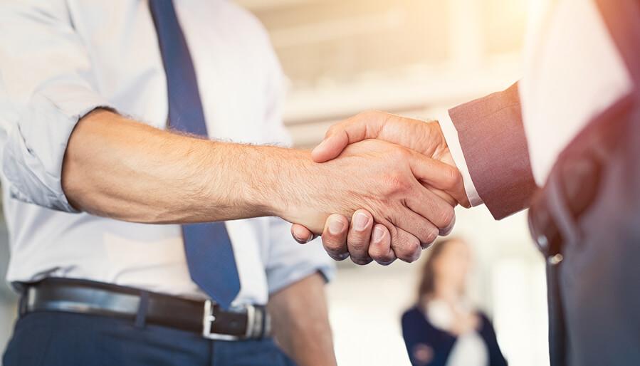 Бизнесмены пожимают друг другу руки во время встречи